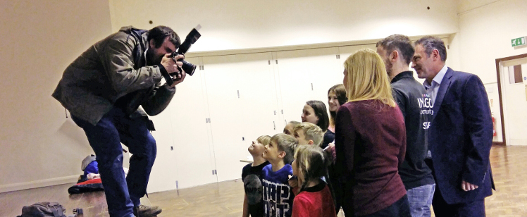 man with camera taking picture of children and adults
