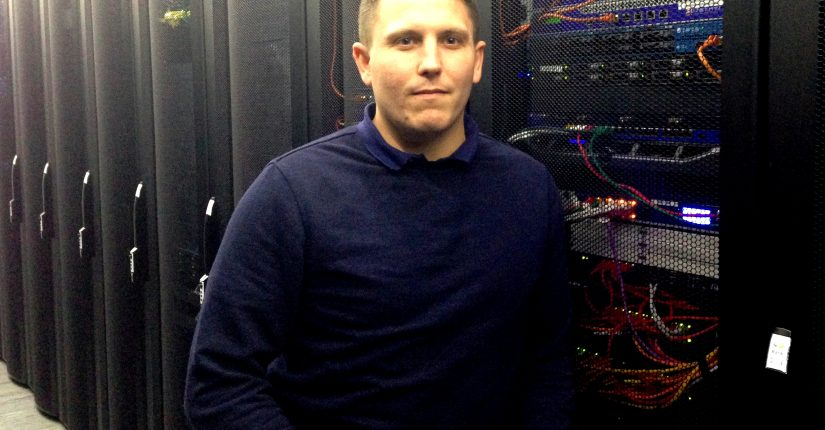 Man in Blue jumper smiling in from to server rack