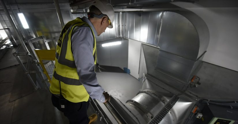 man in high-vis and hard hat looking at metal ducting