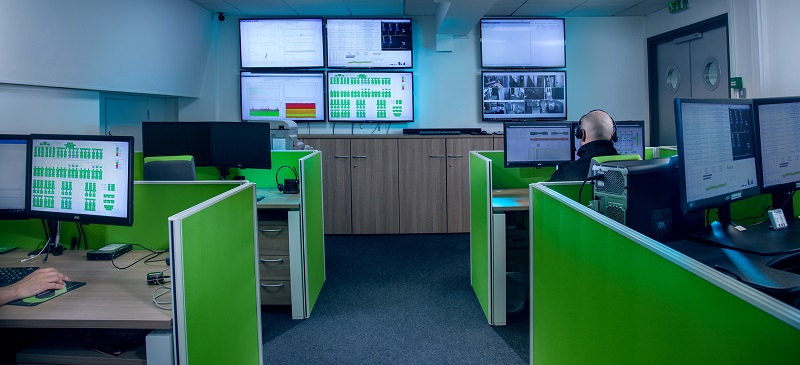 tech office with green room dividers and screen on walls