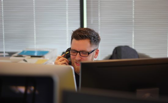 man in office in phone in front of computer screens