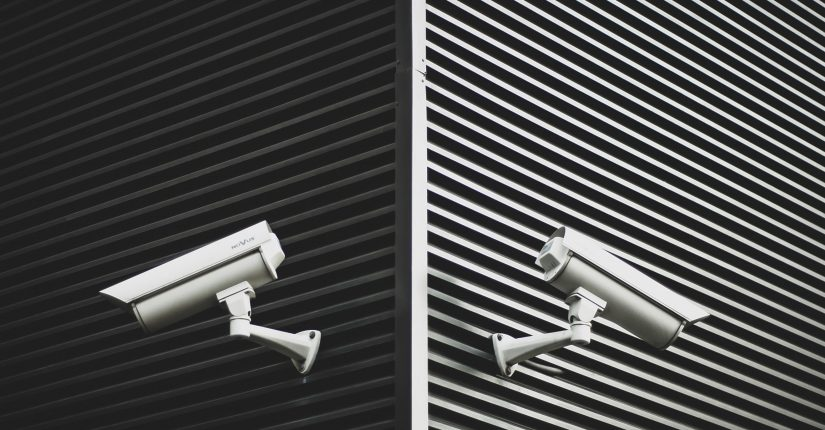 2 white security cameras on black walls